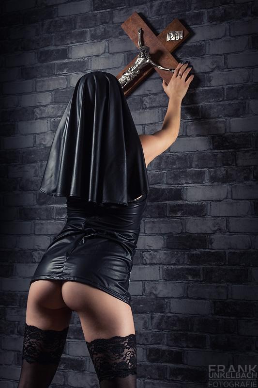 Nonne steht in halterlosen Strümpfen und nacktem Po breitbeinig vor einer Wand und hält ein Kreuz in den Händen.