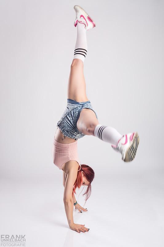 Sportliche Frau mit roten Haaren, Kniestrümpfen, Turnschuhen und Jeans-Hotpants schlägt ein Rad und steht gerade in Handstand.
