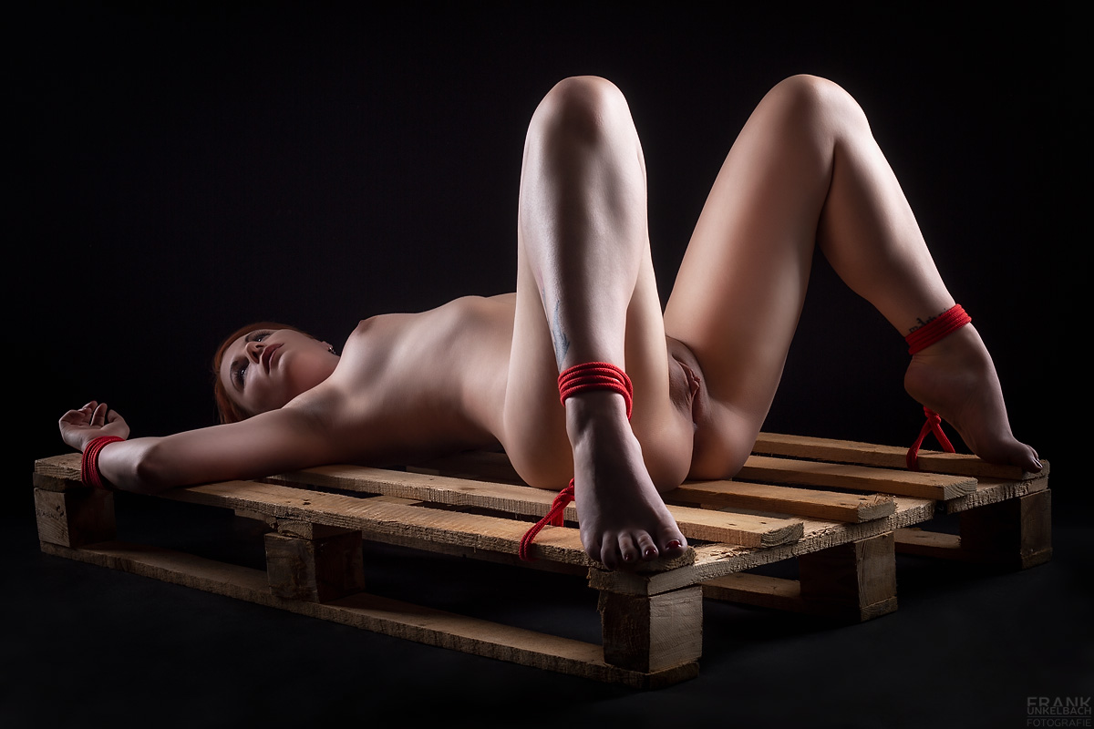 Hilflose nackte Frau wurde mit mit roten Bondage-Seilen breitbeinig auf einer Holzpalette gefesselt.