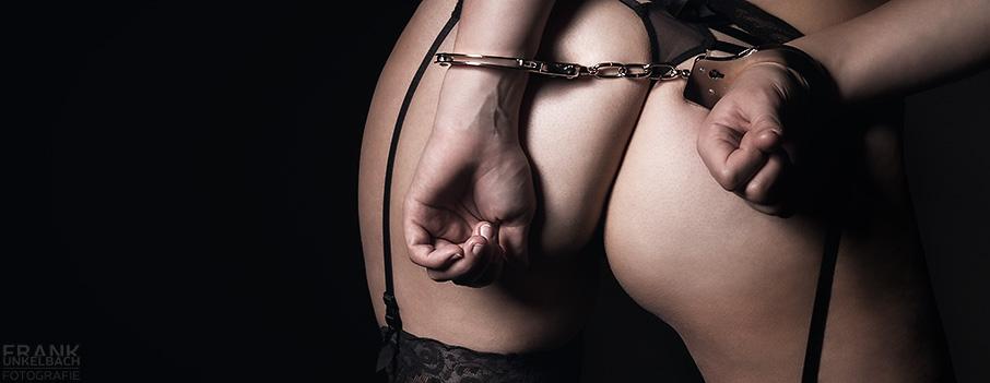 Bodypart-Aufnahme einer auf dem Po mit Handschellen gefesselten Frau. Sie trägt halterlose Strümpfe, Strapse und einen Tanga.