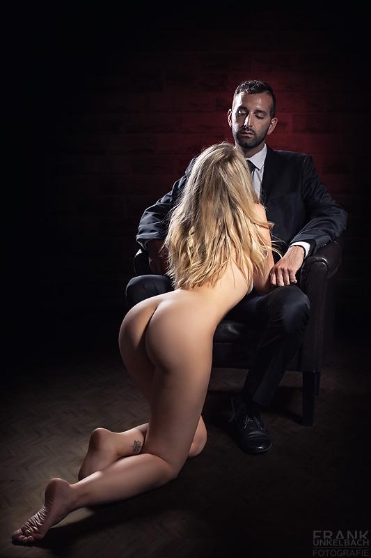 Attraktiver Mann sitzt vollständig bekleidet mit schwarzem Anzug und Krawatte in einem Sessel. Vor ihm auf dem Boden kniet nackt seine Sub.