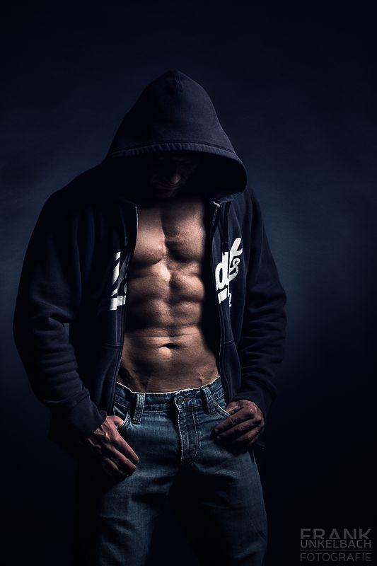 Attraktiver Mann mit Sixpack trägt eine blaue Jeans und einen dunkelblauen Hoodie. Sein Gesicht ist verdeckt. Das Licht betont seinen Waschbrettbauch.