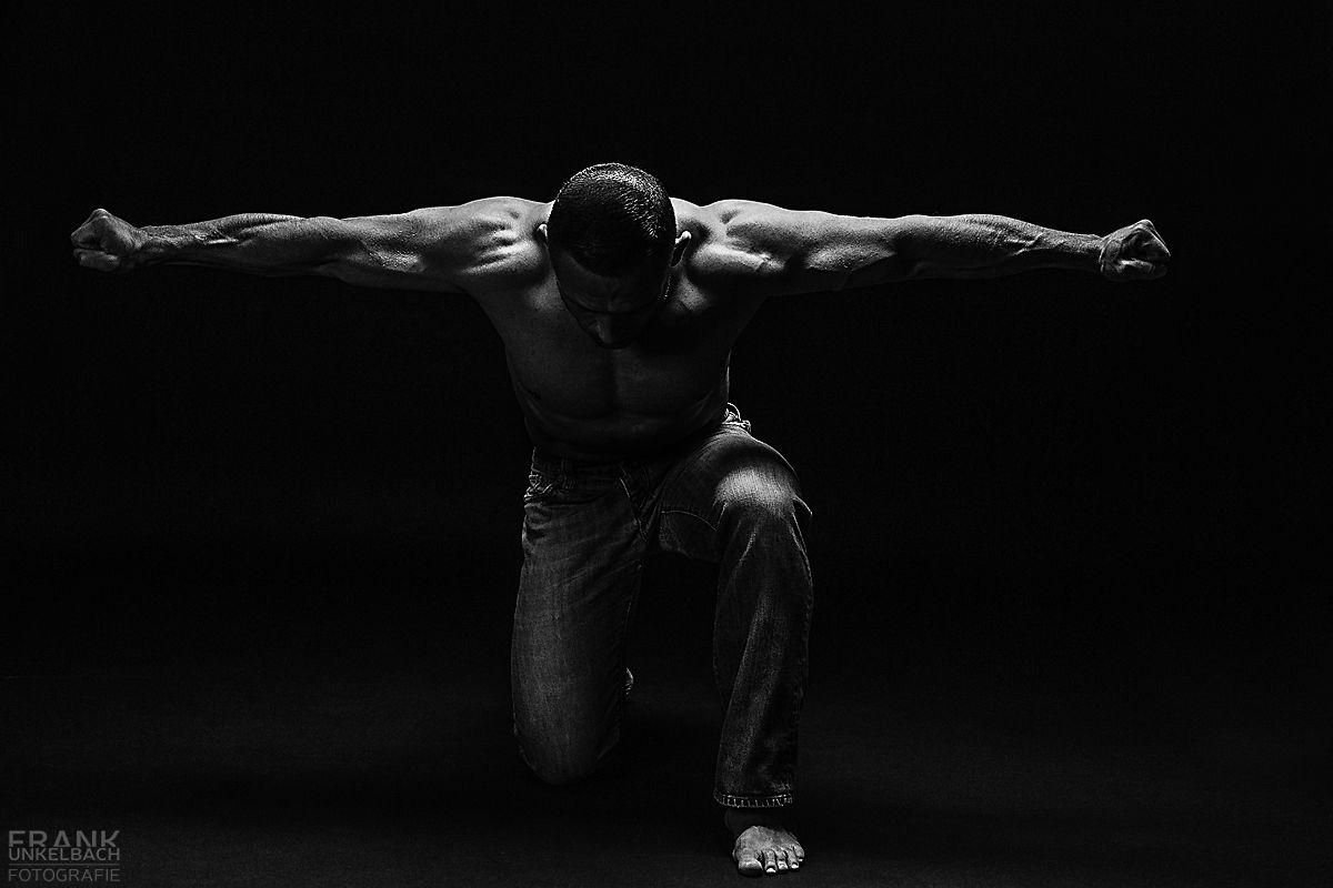 Muskulöser Mann kniet nur mit einer Jeans bekleidet auf dem Boden und streckt die Arm seitlich weit von sich.