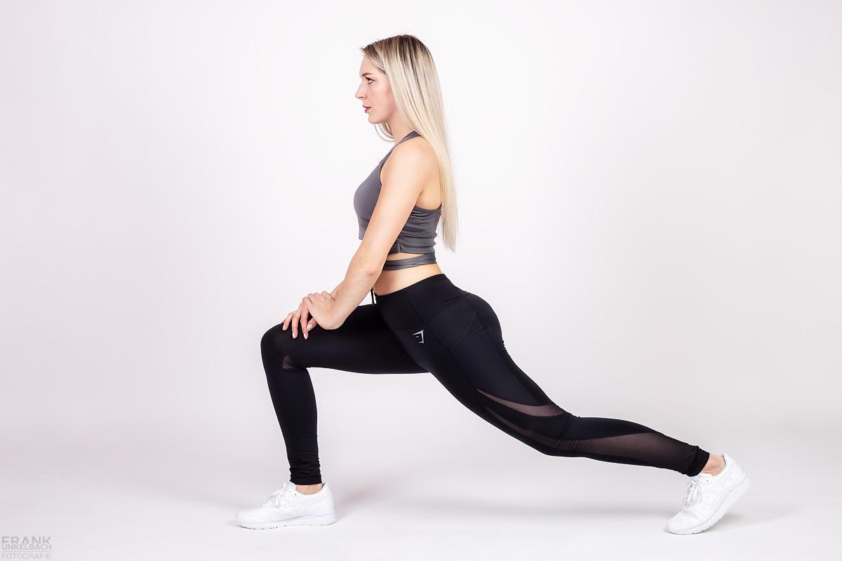 Gut aussehendes Fitness-Model macht vor dem Krafttraining Stretching-Übungen. Beim Ausfallschritt kommt ihr sexy Po gut zur Geltung. Die blonden Haare trägt sie offen.