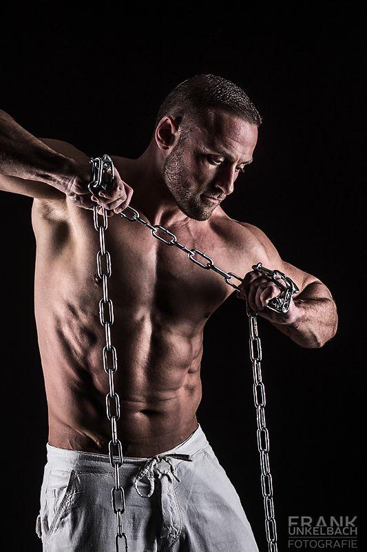 Muskulöser junger man trägt eine weiße Leinenhose und versucht mit aller Kraft eine starke Eisenkette zu zerreißen.