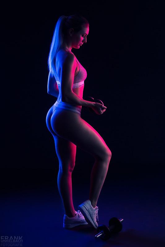Sexy Blondine in grauer Calvin Klein Unterwäsche trainiert Ihre Oberarme mit einer Kurzhantel. Eine weitere Hantel liegt auf dem Boden.