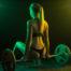 Blondes sexy Fitness-Model mit knackigem Po und Pferdeschwanz sitzt mit schwarzem String-Tanga auf der Stange einer Langhantel.