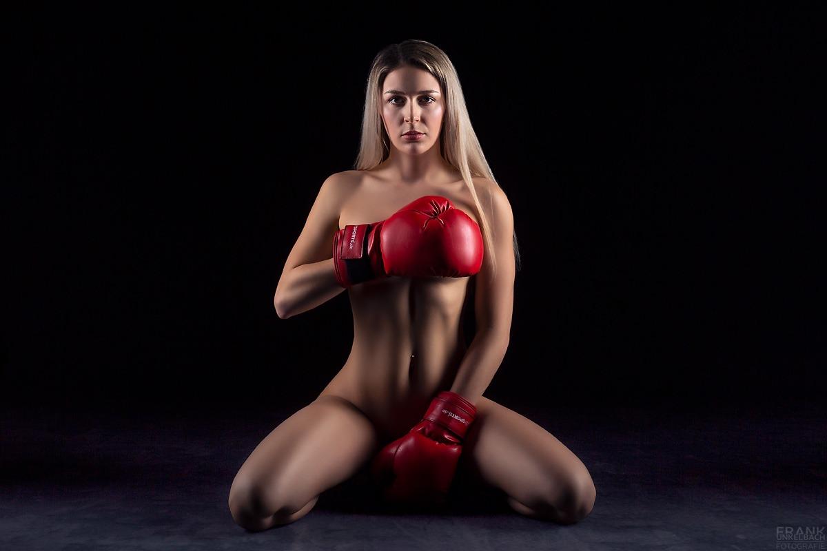 Junge sexy Frau mit schlanker Figur sitzt nur mit Box-Handschuhen bekleidet nackt auf dem Boden.