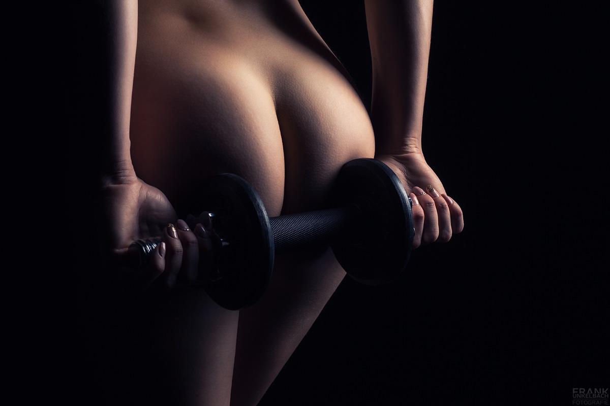 Fitness-Model mit knackigem Po hält eine Kurzhantel in Händen. Ihre Fingernägel sind golden lackiert.