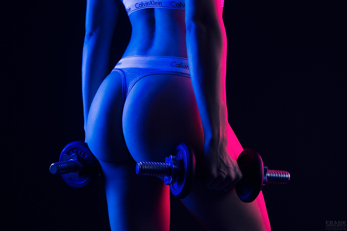 Hübsches Fitness-Model trägt zum Training einen nur sehr knappen Calvin Klein Tanga. In beiden Händen neben ihrem Po hält sie eine Kurzhantel.