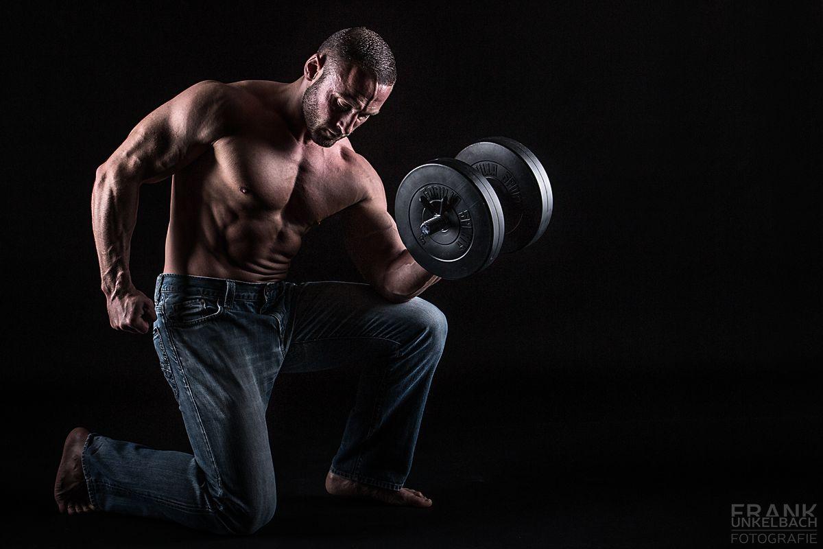 Gut durchtrainierter Mann mit großen Muskeln kniet mit einer blauen Jeans und freiem Oberkörper auf dem Boden und hält eine schwere Hantel.