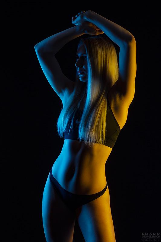 Sexy blondes Fitness-Model trägt schwarze knappe Sport-Unterwäsche und wird von blauem und gelbem Licht angestrahlt, das ihre Kurven perfekt zur Geltung bringt.