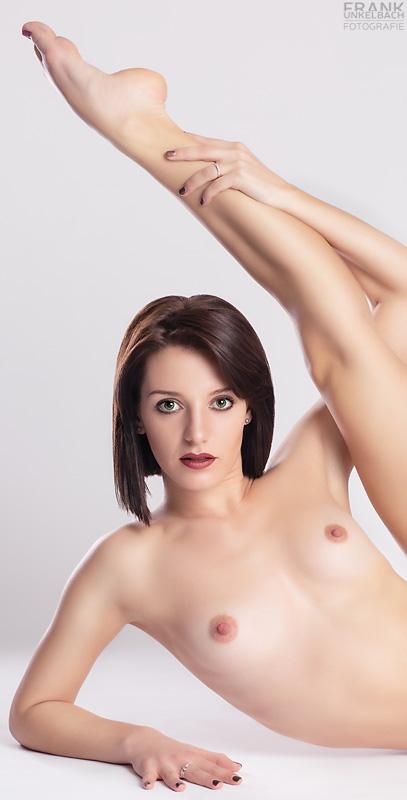 Interessantes Aktportrait einer hübschen Ballerina mit großen Augen. Sie liegt nackt auf dem Boden und hält einen Fuß über ihren Kopf.