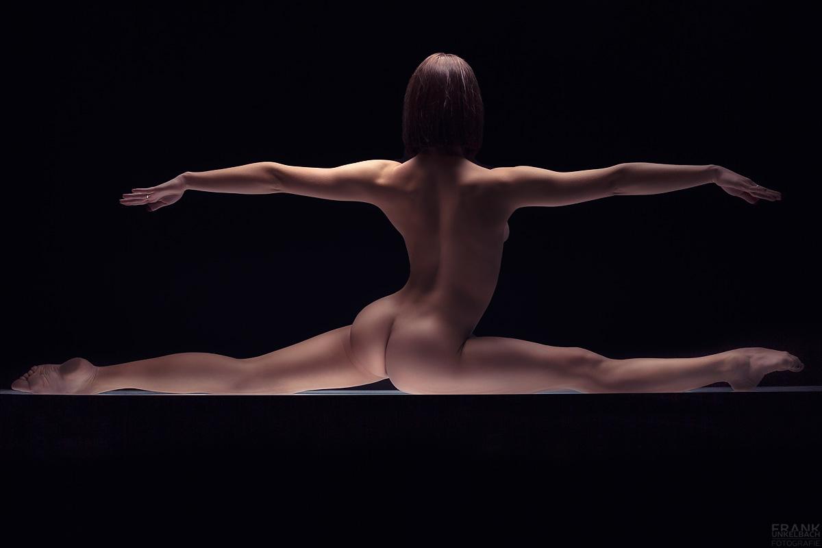 Sexy gelenkige Ballerina macht nackt ein Spagat auf einem Lichttisch. Ihre Arme hält sie parallel zu den Beinen.