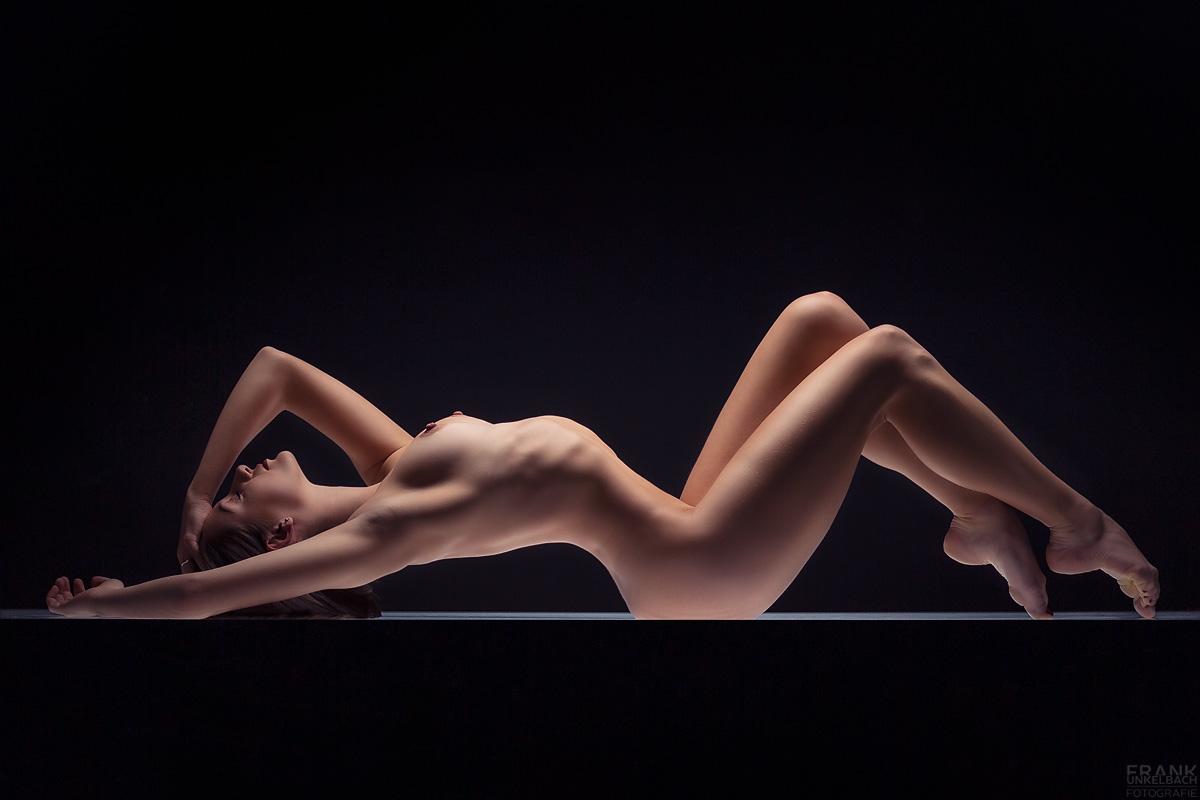 Kurvige Ballerina mit sexy Brüsten und toller Figur liegt nackt im Hohlkreuz auf einem Leuchttisch und greift sich in die Haare.