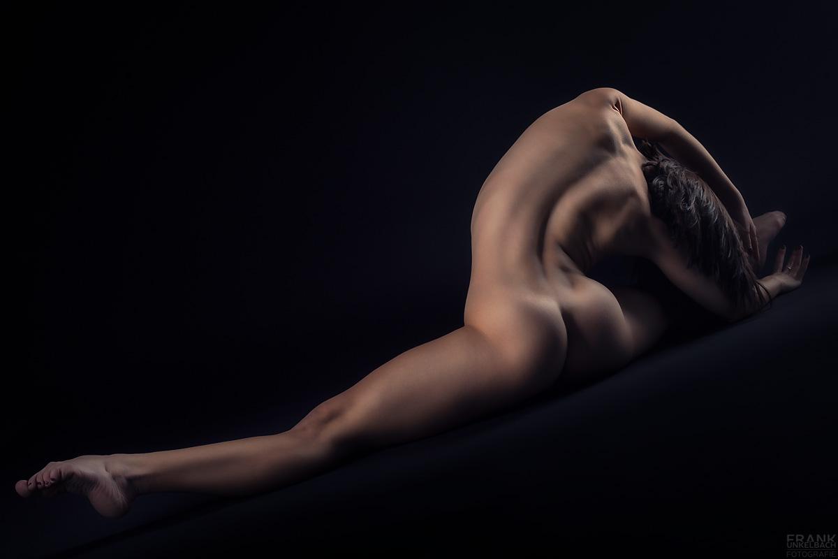 Fuß, Bein, Po und gekrümmter Rücken in perfekter Harmonie. Spagat einer nackten Ballerina mit knackigem Po.