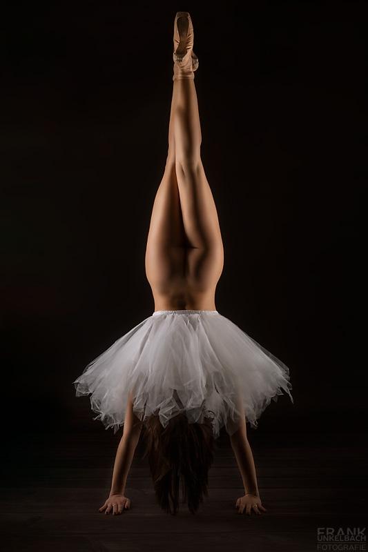 Sexy Ballerina in nichts außer einem Tutu macht einen Handstand bei dem ihre langen Beine mit Spitzenschuhen perfekt zur Geltung kommen.